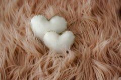 Twee harten in witte die stof op roze haarachtergrond wordt genaaid royalty-vrije stock foto