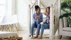 Twee heeft de Afrikaanse Amerikaanse krullende meisjes sistres zitting op treden en pret die samen thuis lachen babbelen Stock Foto