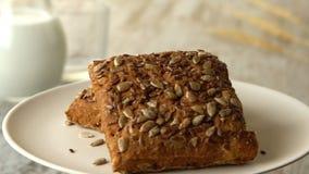 Twee heerlijke eigengemaakte kleine broden van brood met zaden Melk-kruik, op houten rustieke lijst looped stock videobeelden
