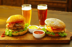 Twee heerlijke hamburgers met rundvlees, ui, tomaat, sla en kaas met ketchup, mosterd en twee glazen bier  Stock Afbeeldingen