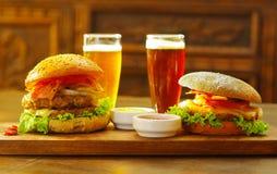 Twee heerlijke hamburgers met rundvlees, ui, tomaat, sla en kaas met ketchup, mosterd en twee glazen bier  Stock Afbeelding