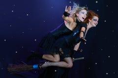 Twee heksen die op bezem vliegen Stock Foto