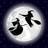 Twee heksen op een achtergrond van de volle maan op Halloween-nacht Stock Afbeelding