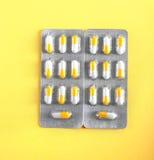 Twee heldere blaren van witte en oranje capsules Pillen op een lichtgele achtergrond Pijnstillers, drugs, antibiotica Stock Foto