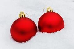 Twee heldere rode Kerstmisbal op sneeuw Stock Foto