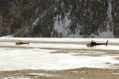 Twee helikopters in het sneeuw behandelde landschap in de alpen Zwitserland Stock Foto