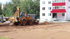 Twee het gele tractorenwerk aangaande bouwwerf stock footage