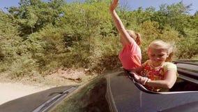 Twee het gelukkige het glimlachen jonge blonden hun deelt golven in beweging van het broedsel van een auto uit tegen het bos stock videobeelden