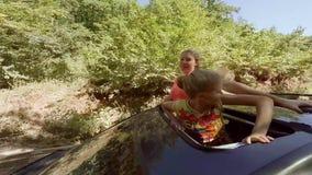 Twee het gelukkige het glimlachen jonge blonden hun deelt golven in beweging van het broedsel van een auto uit tegen het bos stock footage