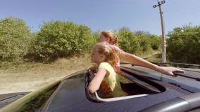Twee het gelukkige jonge blonden lachen die uit broedsel van de auto in beweging tegen het bos springen stock videobeelden