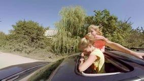 Twee het gelukkige jonge blonden lachen die uit broedsel van de auto in beweging tegen het bos springen stock footage