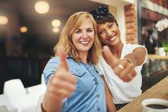 Twee het gelukkige jonge vrouwelijke vrienden geven duimen omhoog royalty-vrije stock afbeeldingen