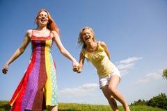 Twee het gelukkige meisjes springen Stock Afbeelding