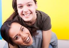 Twee het gelukkige zusters lachen Stock Foto's