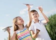 Twee het glimlachen jonge geitjes die met eenvoudige document vliegtuigen spelen Stock Afbeelding