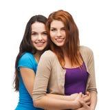 Twee het glimlachen meisjes het koesteren Royalty-vrije Stock Afbeeldingen