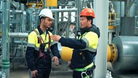 Twee het glimlachen metaalarbeiders bespreken die bij productie-installatieplaats werken stock video