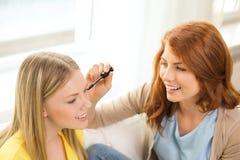 Twee het glimlachen tieners het van toepassing zijn maakt omhoog thuis Stock Afbeelding