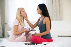 Twee het glimlachen tieners het van toepassing zijn maakt omhoog thuis Royalty-vrije Stock Foto's