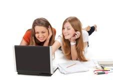 Twee het jonge gelukkige werk van het studentenmeisje aangaande laptop royalty-vrije stock afbeeldingen