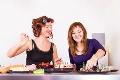 Twee het jonge mooie vrouwenhuisvrouw koken met krulspelden op haar Royalty-vrije Stock Foto