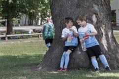 twee het jonge voetballers giechelen die tegen een oude eiken boom leunen Royalty-vrije Stock Foto's