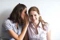 Twee het jonge vrouwen fluisteren stock foto