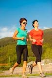 Twee het jonge vrouwen openlucht lopen stock foto