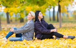 Twee het jonge vrouwen zitten rijtjes in park royalty-vrije stock afbeelding
