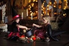 Twee het kleine Halloween-heksen tovert lezen boven pot childh royalty-vrije stock foto's