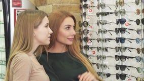 Twee het mooie jonge vrouwen kiezen eyewear in opticienopslag stock videobeelden