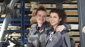 Twee het vrolijke vrouwelijke fabrieksarbeiders koesteren die gelukkig aan de camera glimlachen royalty-vrije stock afbeelding