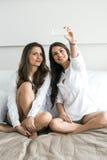 Twee hete meisjes die op een bed liggen die een foto van zich nemen met Royalty-vrije Stock Foto