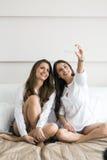Twee hete meisjes die op een bed liggen die een foto van zich nemen met Royalty-vrije Stock Afbeelding