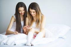 Twee hete meisjes die op een bed liggen die een foto van zich nemen Royalty-vrije Stock Fotografie