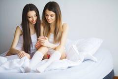 Twee hete meisjes die op een bed liggen die een foto van zich nemen Royalty-vrije Stock Foto