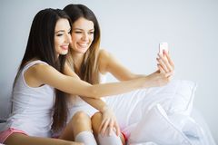 Twee hete meisjes die op een bed liggen die een foto van zich nemen Stock Afbeelding