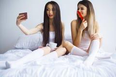 Twee hete meisjes die op een bed liggen die een foto van zich nemen Royalty-vrije Stock Afbeelding