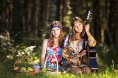 Twee hippiemeisjes met gitaar in een de zomerbos Stock Foto