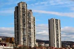 Twee hoge oude wolkenkrabbers die boven veelvoudige familiehuizen en kleinere gebouwen aan kant van kleine heuvel toenemen omring stock fotografie