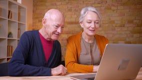 Twee hogere grijs-haired Kaukasische collega's die een video hebben nodigen laptop uit die blij en gelukkig in bureau zijn stock footage
