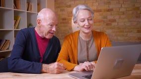 Twee hogere grijs-haired Kaukasische collega's die in videochat op laptop spreken die blij in bureau zijn stock videobeelden
