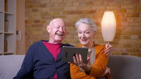 Twee hogere grijs-haired Kaukasische echtgenoten die een video hebben nodigen tablet uit die grappig en blij bij comfortabel huis stock videobeelden