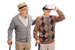 Twee hogere heren die een VR-hoofdtelefoon met behulp van Stock Foto's
