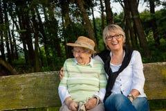 Twee hogere vrouwen die op een bank in een park, conceptengeneraties, familie, zorg zitten stock afbeeldingen