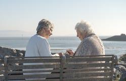 Twee hogere vrouwen die spaanders op een bank eten stock foto