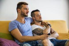 Twee homoseksuelen op bank die thuis omhelzen stock fotografie