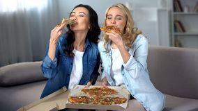 Twee hongerige vrouwelijke studenten die van reusachtige heerlijke pizza genieten binnen, voedsellevering royalty-vrije stock afbeelding