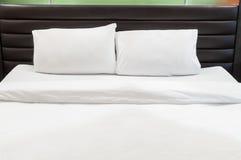 Twee hoofdkussens op bed stock afbeeldingen