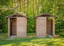 Twee houten die hutten als toiletten worden gebruikt stock afbeelding